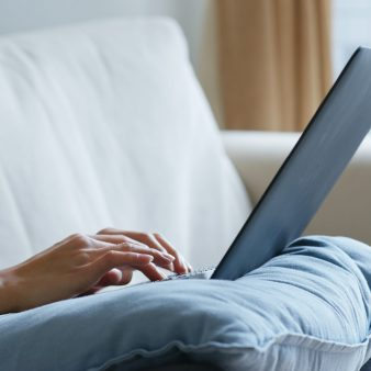 Woman type on notebook computer at home